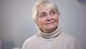 看怀乡年长的妇女单独坐在室和支持,记忆 免版税库存图片