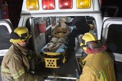 看患者和EMT医生的消防员 库存图片