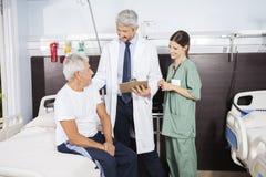 看患者的医生和护士康复中心 免版税库存图片