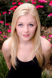 看您在桃红色玫瑰前面的年轻白种人妇女 库存照片