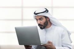 看惊奇他的膝上型计算机的阿拉伯商人 库存图片