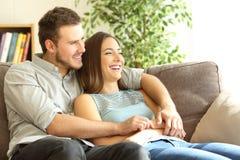 看愉快的夫妇坐长沙发和  免版税库存照片