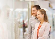 看愉快的夫妇购物在购物中心的窗口 免版税图库摄影