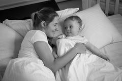 看愉快的母亲的微笑的男婴画象说谎与他在床上 图库摄影