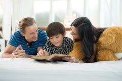 看我的儿子的爸爸和妈妈读书是在Th的床上 免版税库存照片
