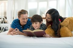 看我的儿子的爸爸和妈妈读书是在Th的床上 库存图片