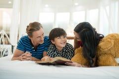 看我的儿子的爸爸和妈妈读书是在Th的床上 免版税库存图片