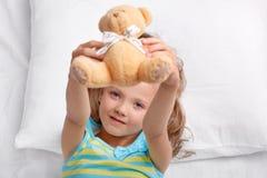 看我的玩具!嬉戏的小逗人喜爱的女性孩子在床上拿着玩具熊,戏剧在唤醒以后,在舒适的枕头的谎言在床上, d 库存照片