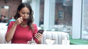 看手机和喝在咖啡馆的亚裔妇女茶 免版税库存图片