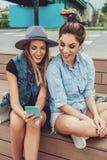 看手机和微笑的女朋友 免版税库存照片