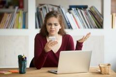看手机和shruggin的沮丧的女性企业家 库存图片