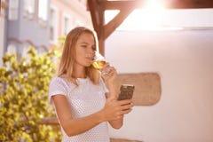 看手机啜饮的啤酒的女孩 图库摄影