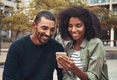 看手机的人举行由她的女朋友 免版税库存照片