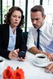 看手机的企业同事,当开会议时 免版税图库摄影