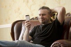 看手机的惊奇的人 库存图片