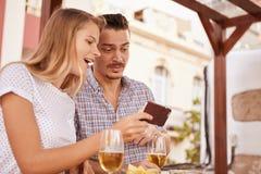 看手机的逗人喜爱的夫妇惊奇 免版税库存图片