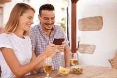 看手机的嘻嘻笑的年轻夫妇 免版税图库摄影