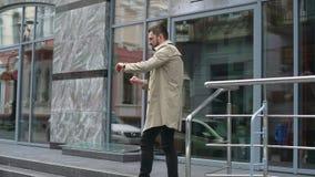 看手表的商人在办公楼中心附近 人晚为工作,会议 股票录像