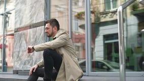 看手表的商人在办公楼中心附近 人晚为工作,会议 影视素材