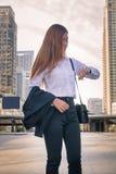 看手表的年轻女商人作为等待的任命 免版税图库摄影