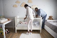 看托儿所轻便小床的母亲和父亲小女儿 免版税库存图片