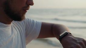 看技术smartwatch巧妙的手表的活跃生活方式人游人 胳膊海滩屏幕的特写镜头宏观关闭在腕子 股票录像