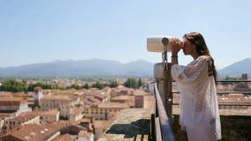 看投入硬币后自动操作双眼在大阳台的美丽的女孩小镇在托斯卡纳,意大利 股票视频