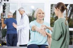看护士的患者在手边投入绉纱绷带 免版税库存图片