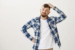 看指示的人,被问 有胡子的迷茫的滑稽的欧洲男学生在蓝色格子花呢上衣 库存照片