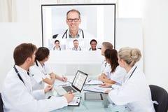 看放映机屏幕的医生队  免版税库存照片