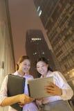 看数字式桌的两名年轻微笑的女实业家户外在晚上 免版税库存图片