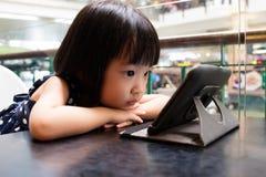 看数字式片剂的亚裔矮小的中国女孩 免版税库存图片
