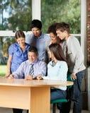 看数字式片剂的学生和老师  免版税库存图片