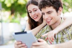 看数字式片剂的青年人 免版税库存照片