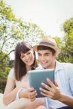 看数字式片剂的年轻夫妇 免版税库存照片