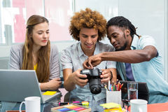 看数字照相机的创造性的年轻商人 免版税图库摄影