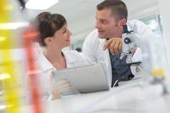 看数字片剂的同事在科学实验室 免版税库存照片