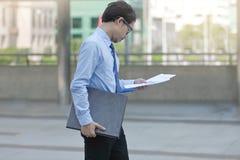 看文书工作或图在他的手上的英俊的年轻亚裔商人侧视图在走到办公室之间 免版税库存照片