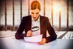 看文件的女实业家的综合图象通过放大镜 库存图片