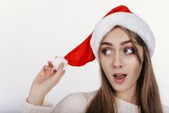 看斜向一边与激发的圣诞节帽子的妇女 库存图片