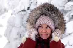 看斜向一边在有绒球的桃红色被编织的帽子和有样式的白色手套的年轻美丽的微笑的女孩在温暖的夹克  库存照片