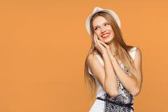 看斜向一边在兴奋的愉快的年轻快乐的妇女 隔绝在橙色背景 免版税库存照片