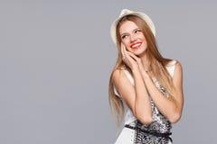 看斜向一边在兴奋的愉快的年轻快乐的妇女 隔绝在灰色 免版税图库摄影