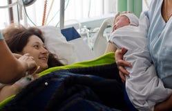 看新出生的婴孩第一次的母亲 免版税图库摄影