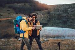看方式的失去的徒步旅行者通过在数字片剂的地图在远足期间 库存照片