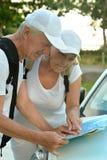 看旅行地图的年长夫妇 库存图片