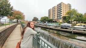 看日内瓦有码头靠码头的小船的塔公寓的女孩 免版税库存图片