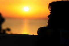 看日落的女孩的剪影海上 库存图片