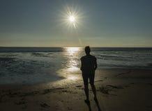 看日落的妇女海滩 库存图片