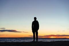 看日落的海滩的一个年轻人 免版税库存照片